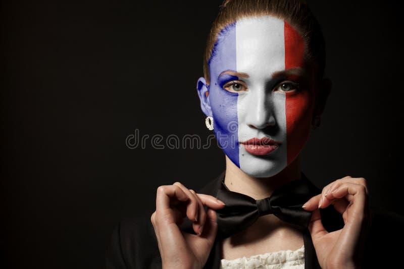 Πορτρέτο της γυναίκας με τη χρωματισμένους σημαία της Γαλλίας και το δεσμό τόξων στοκ φωτογραφία