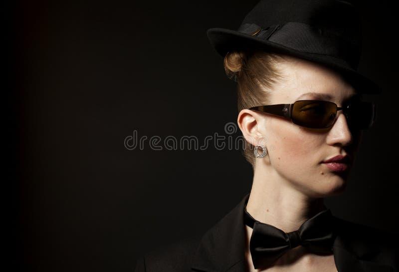Πορτρέτο της γυναίκας με το δεσμό τόξων, το καπέλο και τα γυαλιά ηλίου στοκ φωτογραφίες