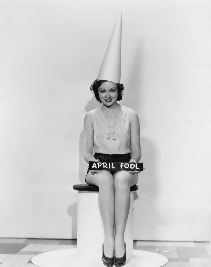 Πορτρέτο της γυναίκας με το σημάδι ανόητων Απριλίου που φορά dunce ΚΑΠ (όλα τα πρόσωπα που απεικονίζονται δεν ζουν περισσότερο κα στοκ φωτογραφία