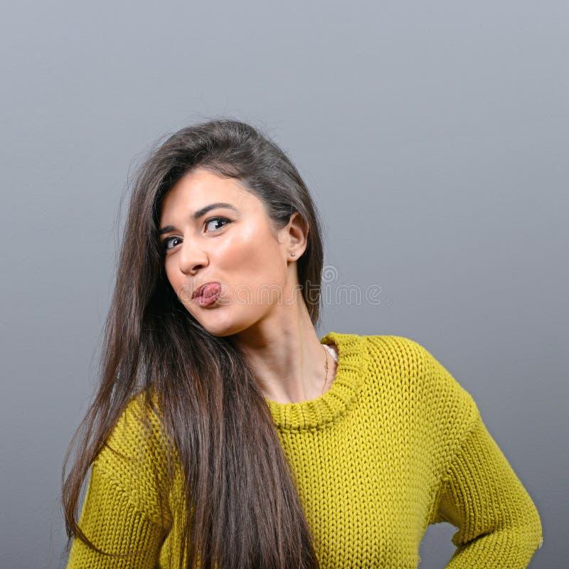 Πορτρέτο της γυναίκας που κολλά έξω τη γλώσσα της στο γκρίζο κλίμα στοκ εικόνες με δικαίωμα ελεύθερης χρήσης