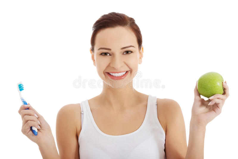 Πορτρέτο της γυναίκας που κρατά ένα μήλο και μια οδοντόβουρτσα στοκ φωτογραφίες