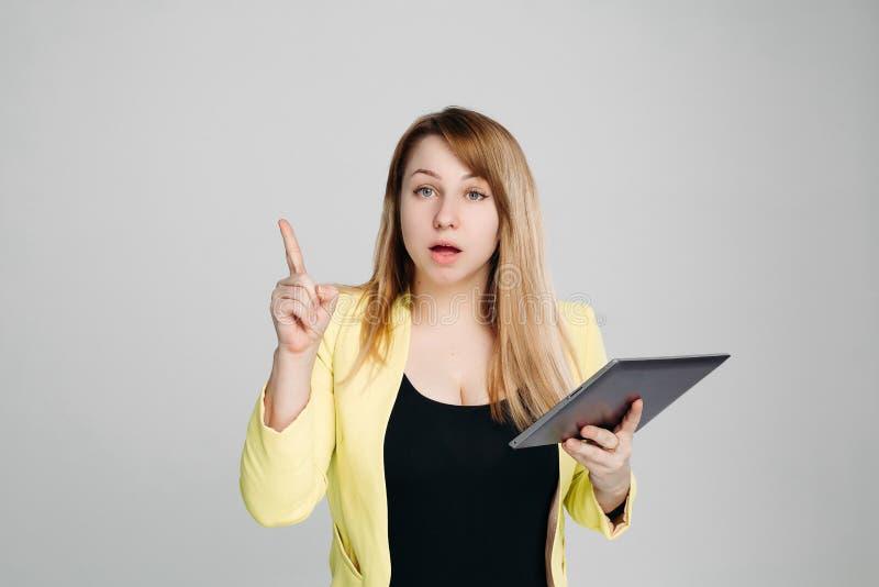 Πορτρέτο της γυναίκας, που κρατά τον υπολογιστή ταμπλετών και που δείχνει το δάχτυλο επάνω στοκ εικόνα με δικαίωμα ελεύθερης χρήσης