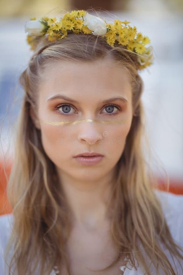 Πορτρέτο της γυναίκας που φορά τα λουλούδια στοκ εικόνα