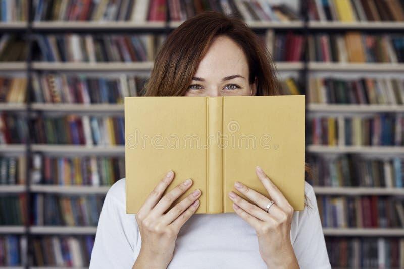 Πορτρέτο της γυναίκας σε ένα πρόσωπο βιβλιοθηκών μισό-που καλύπτεται από το ανοιγμένο βιβλίο, μακρυμάλλες Νέο κορίτσι φοιτητών πα στοκ φωτογραφία με δικαίωμα ελεύθερης χρήσης