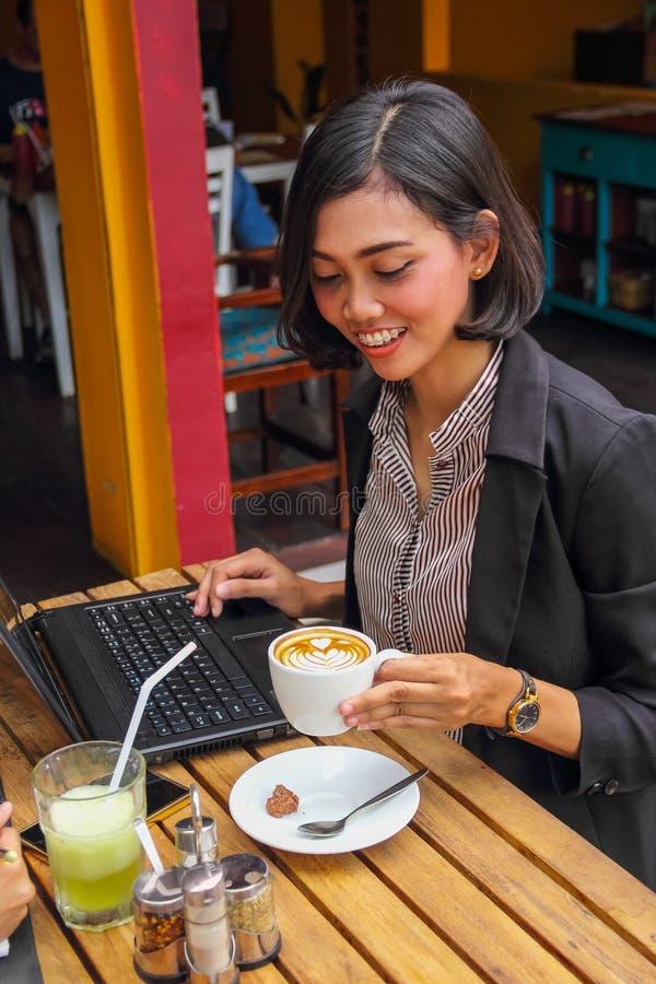 Πορτρέτο της γυναίκας σταδιοδρομίας στο διάλειμμά της που πίνει ένα φλυτζάνι του cappuccino στοκ εικόνα