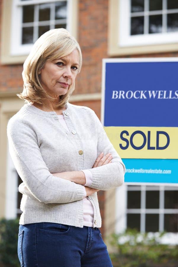 Πορτρέτο της δυστυχισμένης ώριμης γυναίκας που αναγκάζεται να πωλήσει το σπίτι μέσω των οικονομικών προβλημάτων στοκ φωτογραφία