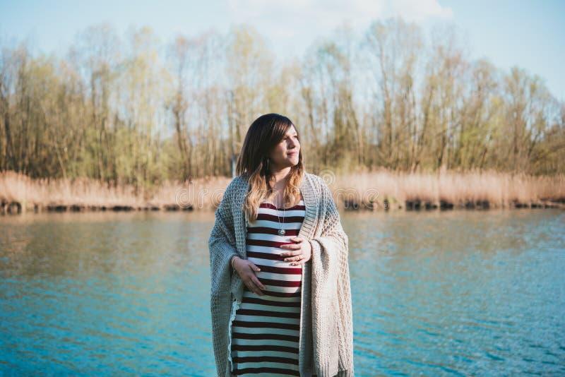 Πορτρέτο της εγκύου γυναίκας στην ακτή στον ποταμό στοκ εικόνα