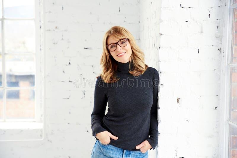Πορτρέτο της ελκυστικής γυναίκας που φορά το πουλόβερ και τα τζιν λαιμών ρόλων εξετάζοντας τη κάμερα και το χαμόγελο στοκ φωτογραφία