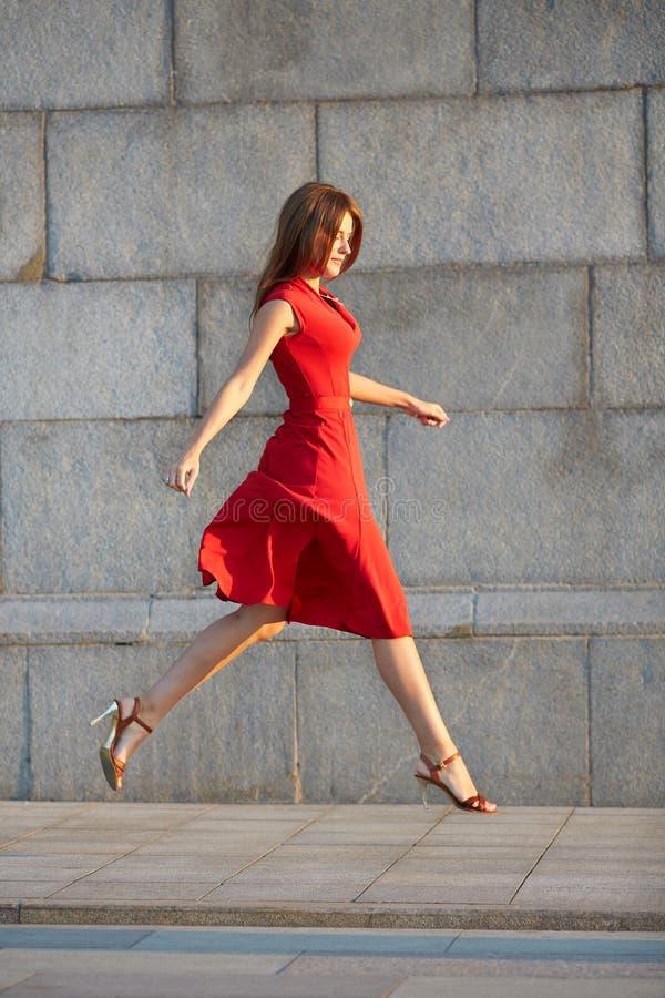 Πορτρέτο της ελκυστικής κομψής νέας γυναίκας σε ένα κόκκινο φόρεμα, που πηδά στο πεζοδρόμιο στοκ φωτογραφίες