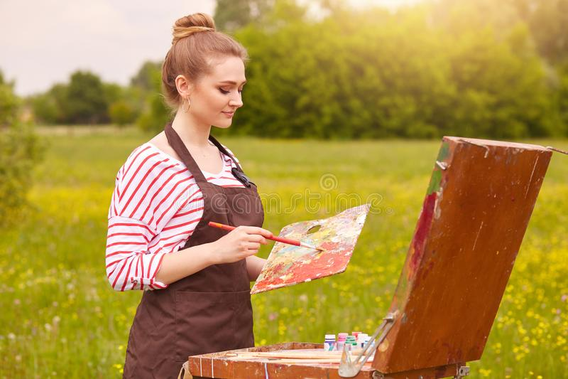 Πορτρέτο της ελκυστικής νέας γυναίκας που φορά το άσπρο πουκάμισο με τα κόκκινα λωρίδες και την καφετιά ποδιά, κρατώντας την παλέ στοκ εικόνες