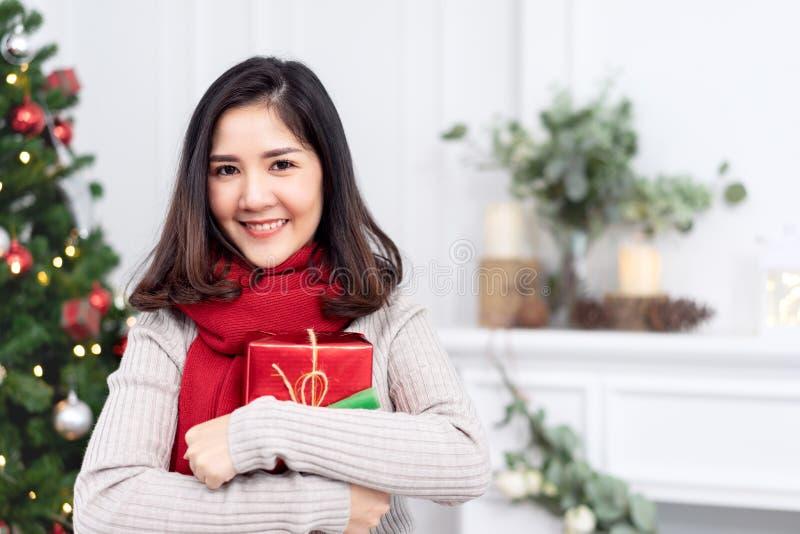Πορτρέτο της ελκυστικού νέου ασιατικού γυναίκας ή του έφηβη που χαμογελά και που εξετάζει τη κάμερα που κρατά το κόκκινο δώρο ή τ στοκ εικόνες