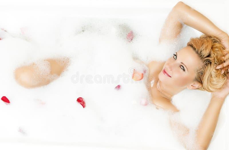 Πορτρέτο της εμπαθούς δελεαστικής αισθησιακής καυκάσιας ξανθής στήριξης στη Foamy μπανιέρα που γεμίζουν με τα ροδαλά πέταλα στοκ φωτογραφίες
