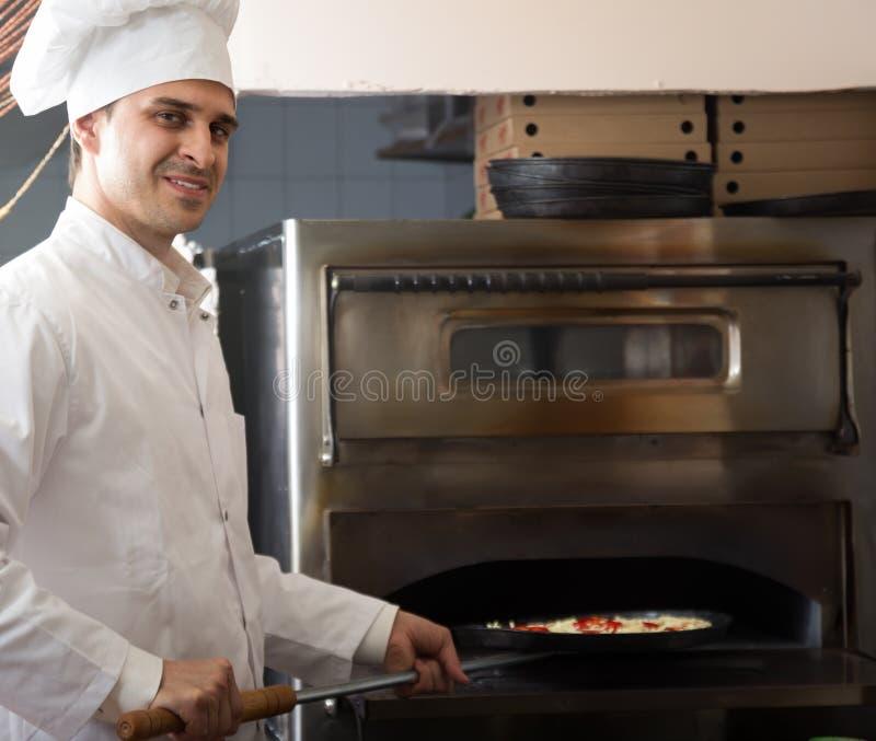 Πορτρέτο της επαγγελματικής νέας αρσενικής πίτσας ψησίματος αρχιμαγείρων στοκ εικόνες