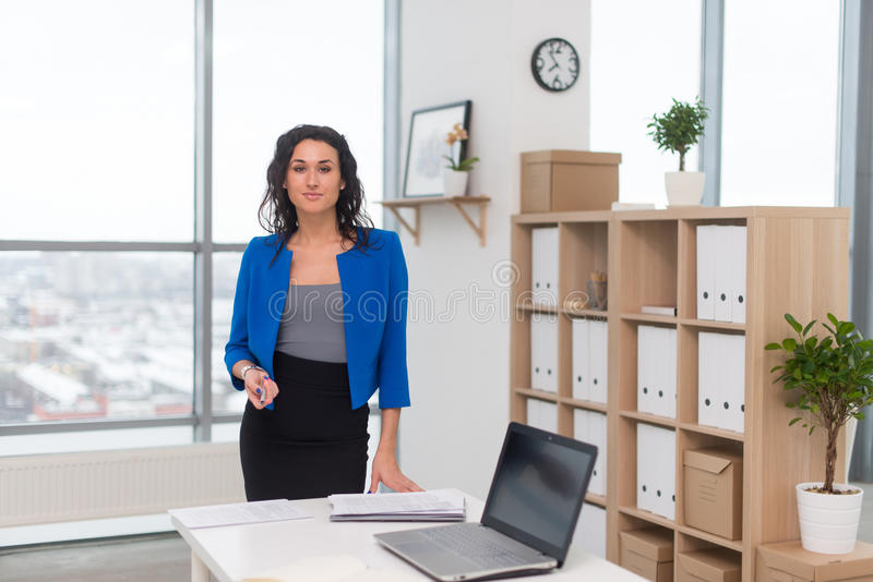 Πορτρέτο της επιχειρηματία στο γραφείο που φαίνεται βέβαιο και που χαμογελά στοκ φωτογραφία με δικαίωμα ελεύθερης χρήσης