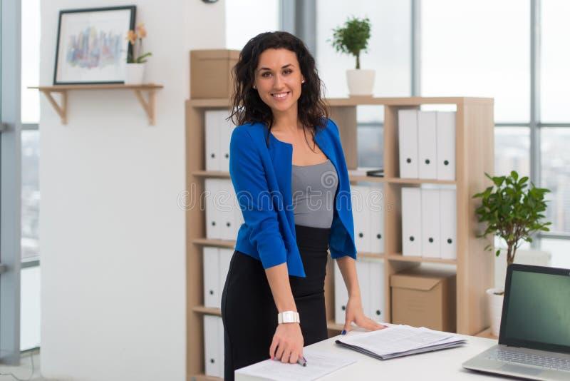 Πορτρέτο της επιχειρηματία στο γραφείο που φαίνεται βέβαιο και που χαμογελά στοκ εικόνα