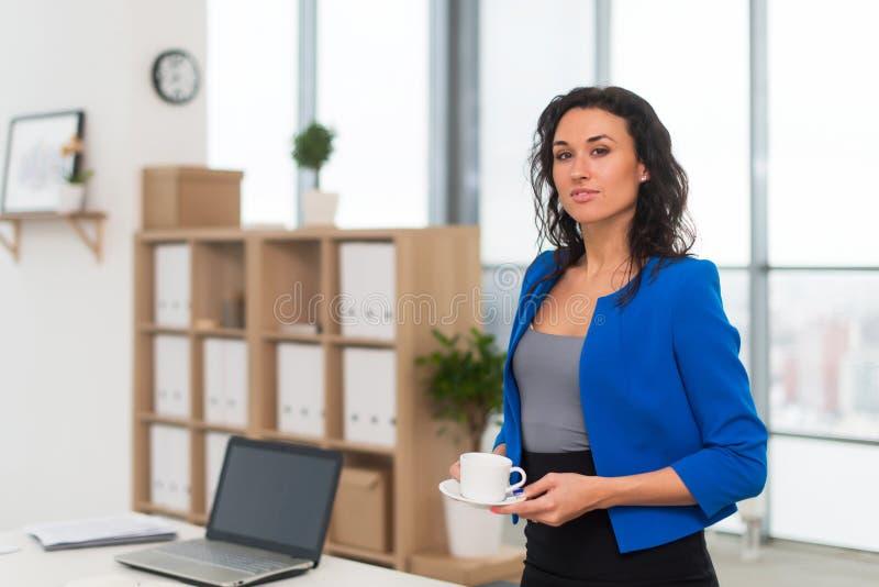 Πορτρέτο της επιχειρηματία στο γραφείο που φαίνεται βέβαιο και που χαμογελά στοκ εικόνες