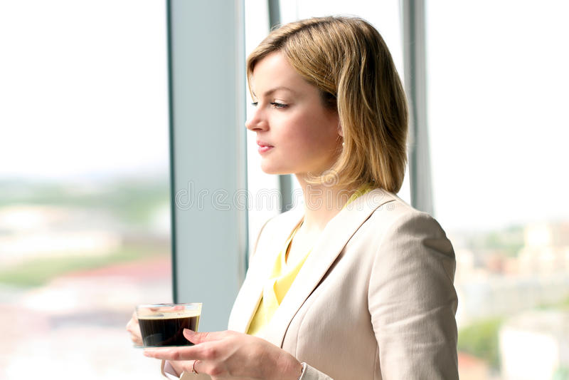 Πορτρέτο της επιχειρησιακής γυναίκας που στέκεται με τον καφέ κοντά στο παράθυρο στοκ εικόνες