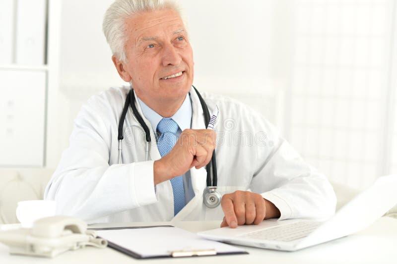 Πορτρέτο της εργασίας γιατρών με το lap-top στο γραφείο του στοκ φωτογραφίες με δικαίωμα ελεύθερης χρήσης