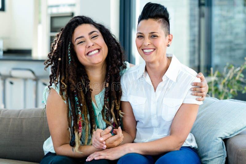 Πορτρέτο της λεσβιακής συνεδρίασης ζευγών μαζί στον καναπέ και το χαμόγελο στοκ εικόνα