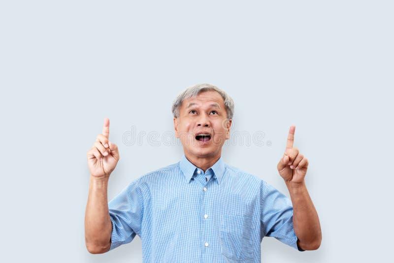 Πορτρέτο της ευτυχούς ανώτερης ασιατικής χειρονομίας ή της υπόδειξης ατόμων του χεριού και του δάχτυλου επάνω και της εξέτασης αν στοκ φωτογραφίες με δικαίωμα ελεύθερης χρήσης