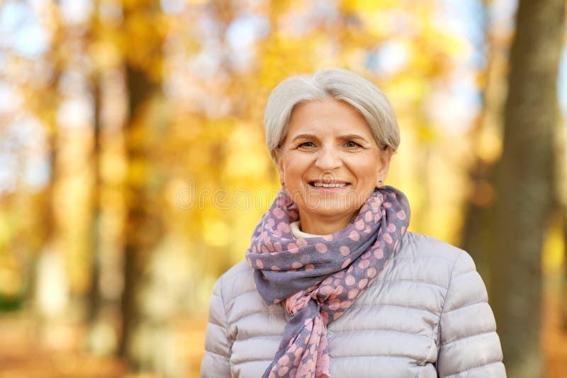 Πορτρέτο της ευτυχούς ανώτερης γυναίκας στο πάρκο φθινοπώρου στοκ φωτογραφίες