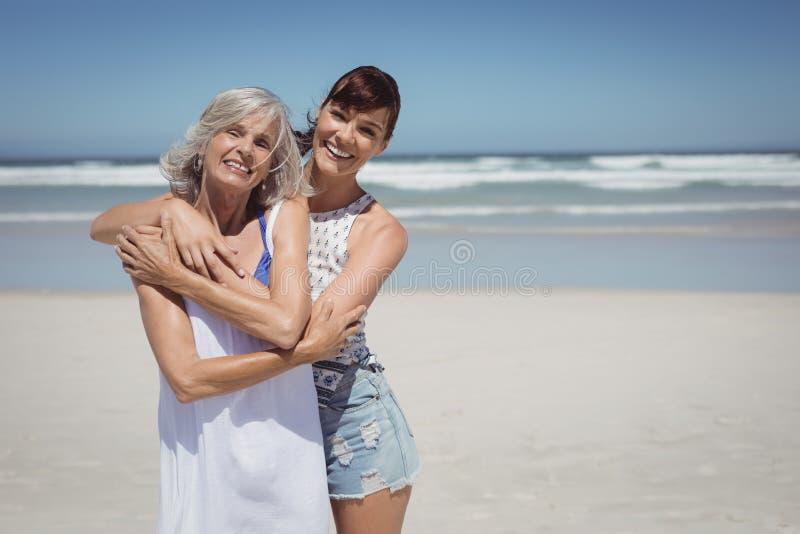 Πορτρέτο της ευτυχούς γυναίκας με τη μητέρα της που στέκεται στην παραλία στοκ εικόνες