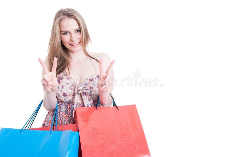 Πορτρέτο της ευτυχούς γυναίκας με τις τσάντες που κάνουν το διπλό σημάδι νίκης στοκ φωτογραφία με δικαίωμα ελεύθερης χρήσης
