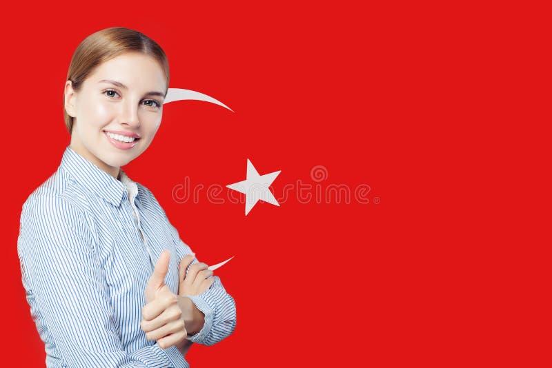 Πορτρέτο της ευτυχούς γυναίκας με τον αντίχειρα επάνω στο τουρκικό υπόβαθρο σημαιών Ταξίδι ή επιχείρηση στην Τουρκία στοκ φωτογραφίες με δικαίωμα ελεύθερης χρήσης