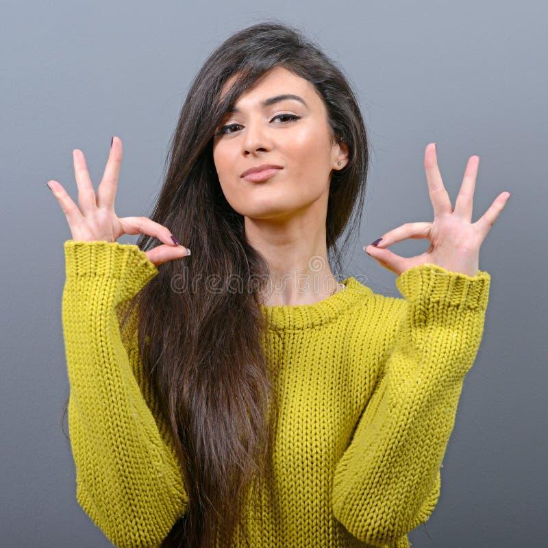 Πορτρέτο της ευτυχούς γυναίκας που παρουσιάζει εντάξει σημάδι στο γκρίζο κλίμα στοκ εικόνες με δικαίωμα ελεύθερης χρήσης