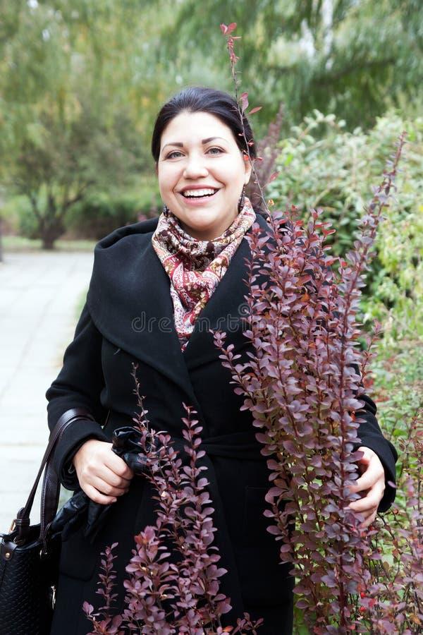 Πορτρέτο της ευτυχούς γυναίκας στο πάρκο στοκ εικόνες