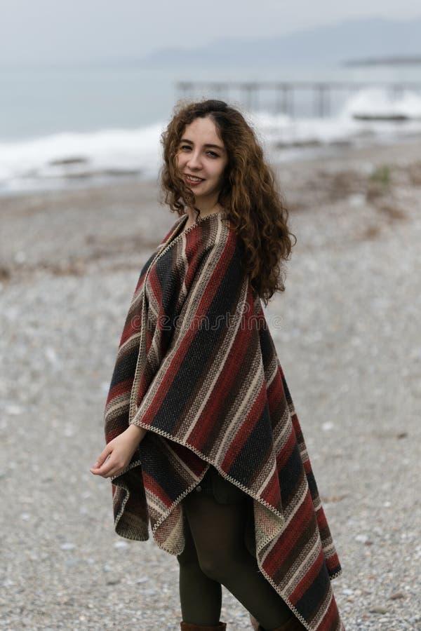 Πορτρέτο της ευτυχούς γυναίκας brunette στην παραλία που φορά poncho στοκ φωτογραφίες με δικαίωμα ελεύθερης χρήσης