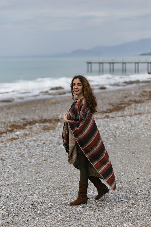 Πορτρέτο της ευτυχούς γυναίκας brunette στην παραλία που φορά poncho στοκ εικόνα