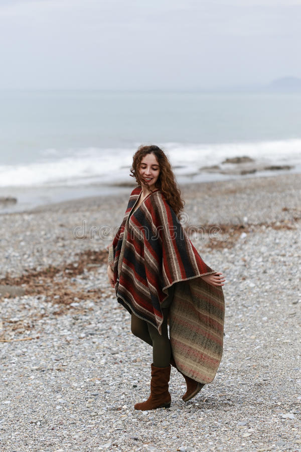 Πορτρέτο της ευτυχούς γυναίκας brunette στην παραλία που φορά poncho στοκ εικόνες