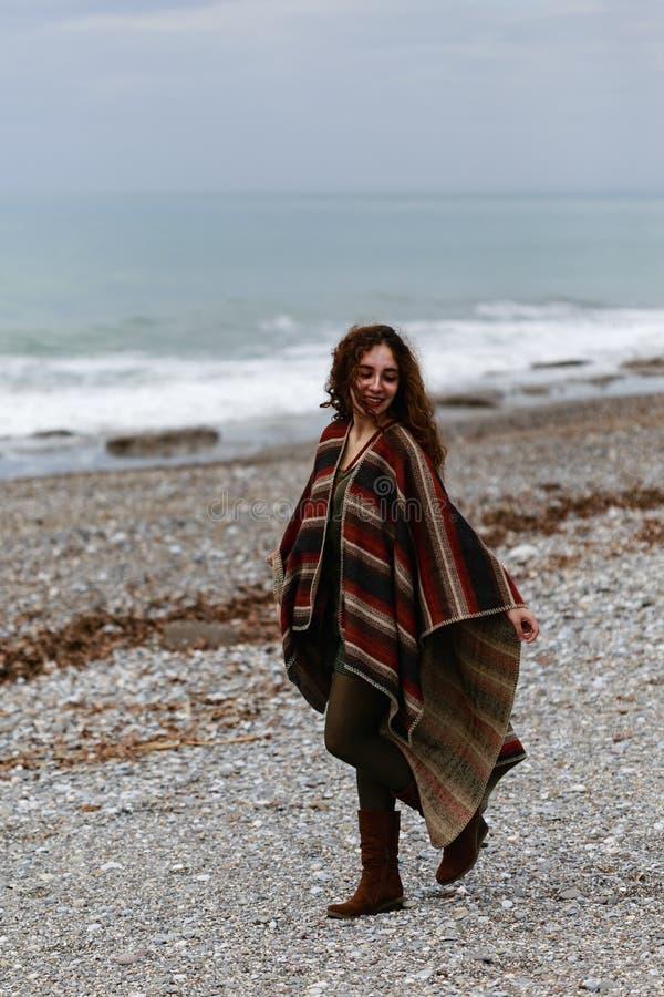 Πορτρέτο της ευτυχούς γυναίκας brunette στην παραλία που φορά poncho στοκ εικόνες με δικαίωμα ελεύθερης χρήσης