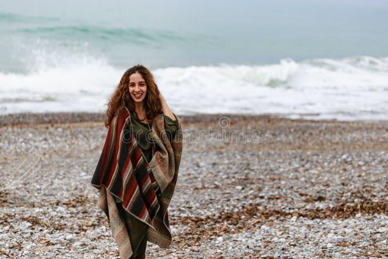 Πορτρέτο της ευτυχούς γυναίκας brunette στην παραλία που φορά poncho στοκ φωτογραφία με δικαίωμα ελεύθερης χρήσης