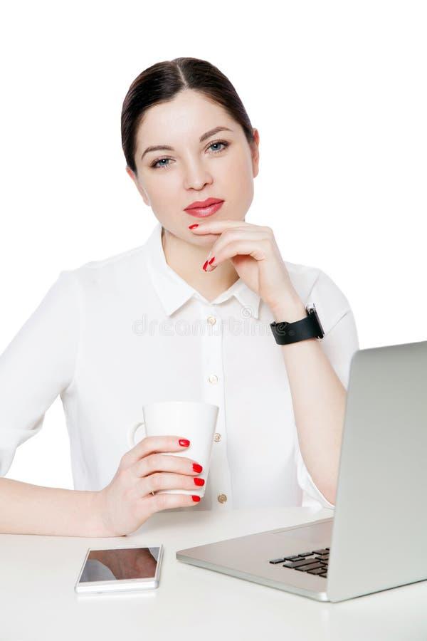 Πορτρέτο της ευτυχούς ελκυστικής επιχειρηματία brunette στην άσπρη συνεδρίαση πουκάμισων, φλυτζάνι εκμετάλλευσης του ποτού, σχετι στοκ εικόνα