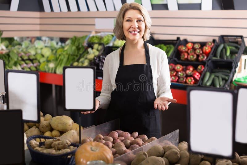 Πορτρέτο της ευτυχούς ενήλικης εργασίας γυναικών στο παντοπωλείο στοκ φωτογραφίες