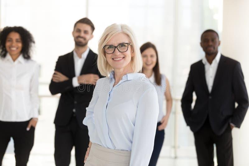 Πορτρέτο της ευτυχούς επιχείρησης CEO ηλικιωμένων γυναικών με τη διαφορετική ομάδα στοκ φωτογραφία με δικαίωμα ελεύθερης χρήσης