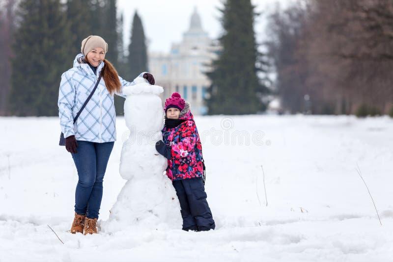 Πορτρέτο της ευτυχούς ευρωπαϊκής μητέρας και της κόρης της που στέκονται κοντά στο μικρό χιονάνθρωπο, χειμερινή εποχή, διάστημα α στοκ εικόνα με δικαίωμα ελεύθερης χρήσης