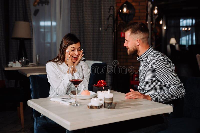 Πορτρέτο της ευτυχούς και έκπληκτης νέας λήψης γυναικών παρούσας από το φίλο καθμένος στον καφέ στοκ εικόνες