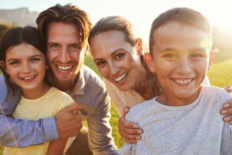 Πορτρέτο της ευτυχούς λευκιάς οικογένειας που αγκαλιάζει υπαίθρια, αναδρομικά φωτισμένο στοκ φωτογραφίες με δικαίωμα ελεύθερης χρήσης