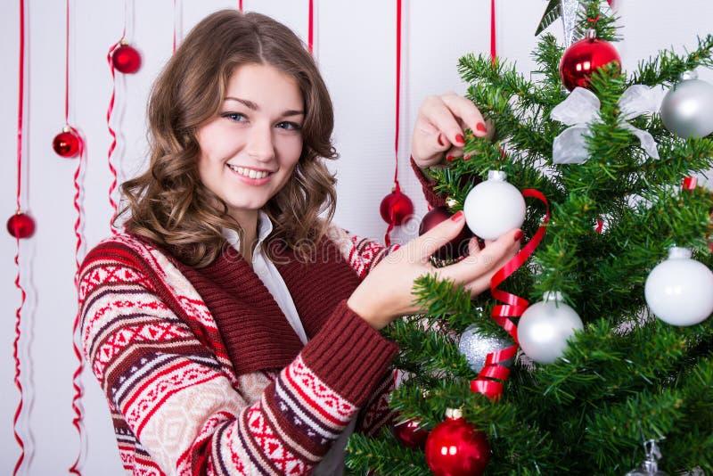 Download Πορτρέτο της ευτυχούς νέας γυναίκας που διακοσμεί το χριστουγεννιάτικο δέντρο Στοκ Εικόνες - εικόνα από αρκετά, διακοσμήστε: 62701380