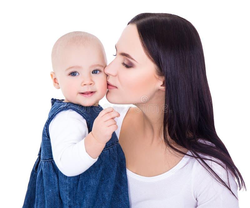 Πορτρέτο της ευτυχούς νέας μητέρας που φιλά λίγη κόρη που απομονώνεται στοκ εικόνες