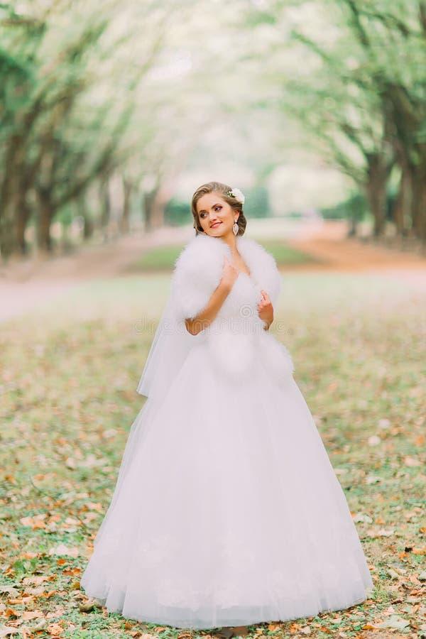 Πορτρέτο της ευτυχούς ξανθής νύφης άσπρο boa φορεμάτων και γουνών στην πάροδο στο πάρκο φθινοπώρου στοκ φωτογραφία
