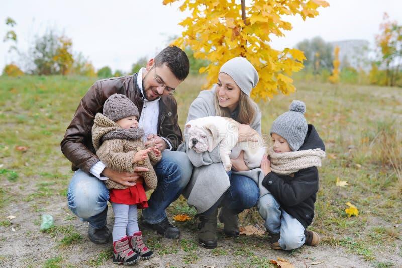 Πορτρέτο της ευτυχούς οικογένειας: Μητέρα, πατέρας, παιδιά και κουτάβι δύο του μπουλντόγκ υπαίθρια Φθινόπωρο υπαίθρια στοκ εικόνες με δικαίωμα ελεύθερης χρήσης