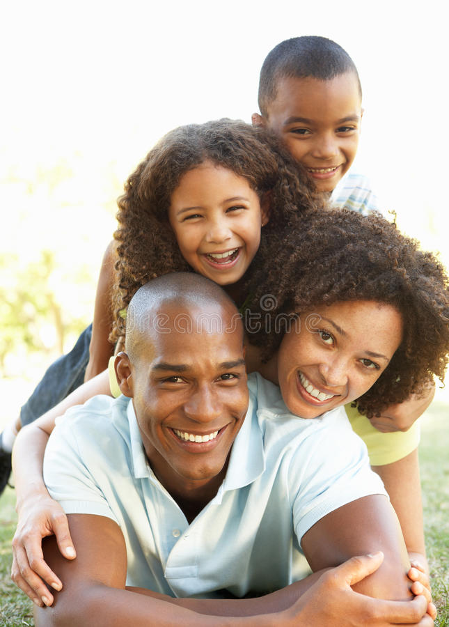 Πορτρέτο της ευτυχούς οικογένειας που συσσωρεύεται επάνω στο πάρκο στοκ φωτογραφία με δικαίωμα ελεύθερης χρήσης