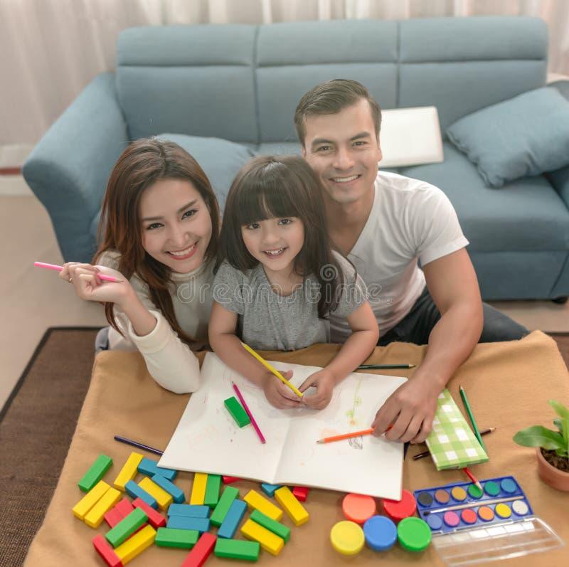 Πορτρέτο της ευτυχούς οικογενειακής κόρης και του σχεδίου και της ανάγνωσης γονέων από κοινού στοκ εικόνα με δικαίωμα ελεύθερης χρήσης