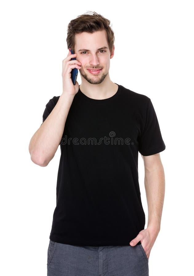 Πορτρέτο της ευτυχούς ομιλίας νεαρών άνδρων στο τηλέφωνο κυττάρων που απομονώνεται στο wh στοκ εικόνες με δικαίωμα ελεύθερης χρήσης