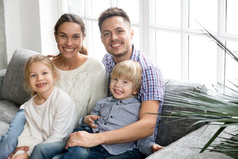 Πορτρέτο της ευτυχούς πολυ-εθνικής οικογένειας που αγκαλιάζει τα υιοθετημένα παιδιά bon στοκ φωτογραφία με δικαίωμα ελεύθερης χρήσης