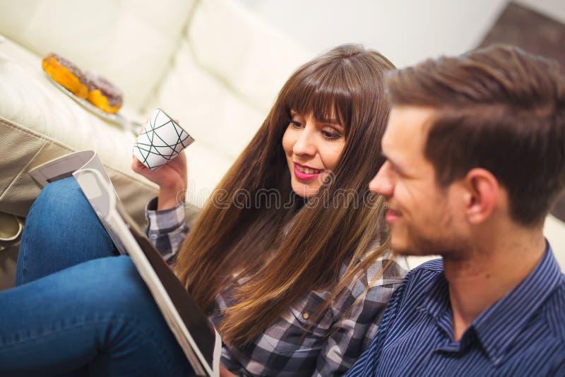 Πορτρέτο της ευτυχούς συνεδρίασης ζευγών στον καναπέ και της ανάγνωσης ένα περιοδικό στοκ φωτογραφίες με δικαίωμα ελεύθερης χρήσης